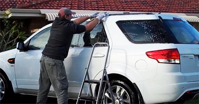 丁寧な手洗い洗車をするカーショップの男性