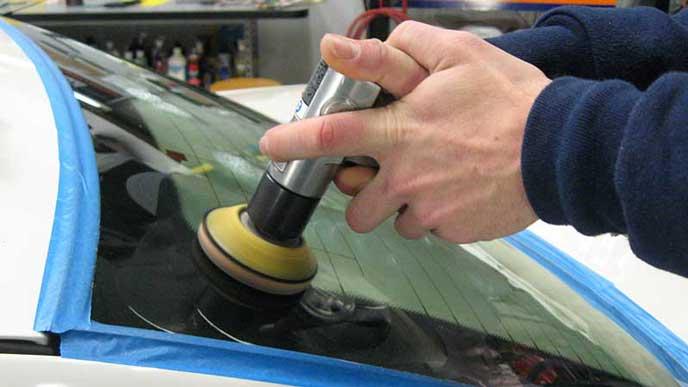 フロントガラスのウロコ汚れを除去する整備士