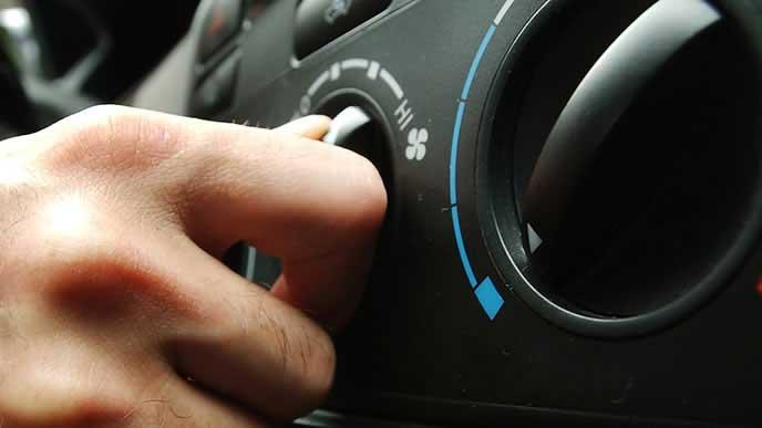 常に自動車のエアコンを付ける男性
