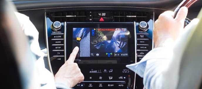 カーナビのモニターを参考に駐車するドライバー