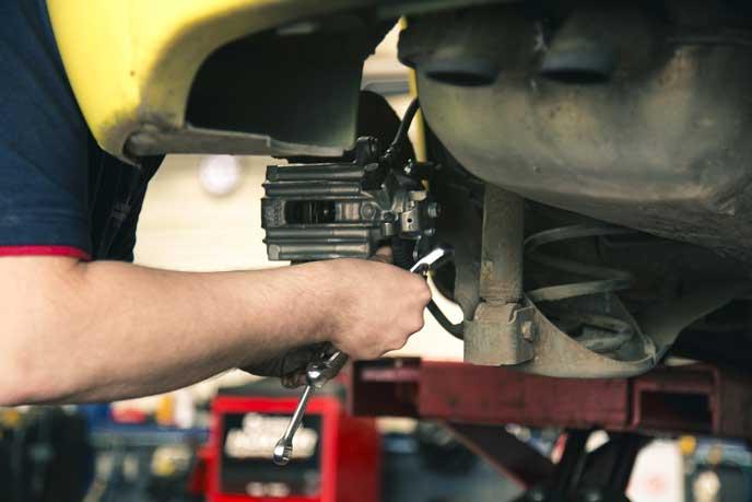 車のブレーキの点検をする整備士