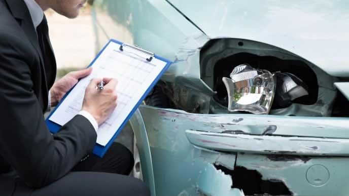 車の故障状況を確認する保険外交員