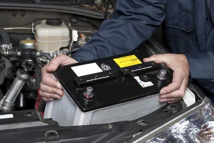 バッテリーを持ち上げる整備士