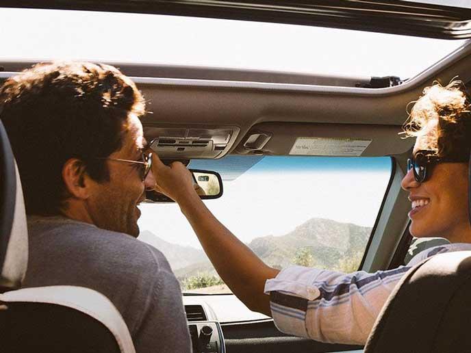 サンルーフを開けてドライブするカップル