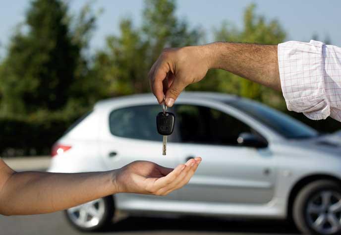 オーナーに車の鍵を渡す車屋さん