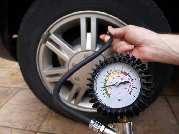 タイヤの空気圧を調べる男性