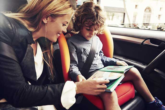 助手席に乗った子どもに絵本を読んであげる女性