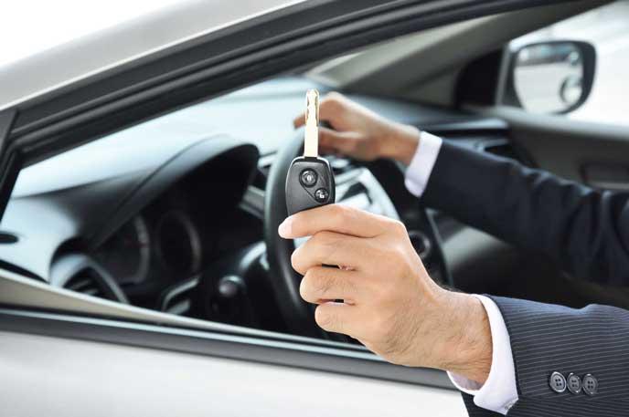 利用者に鍵を渡すレンタカー業者