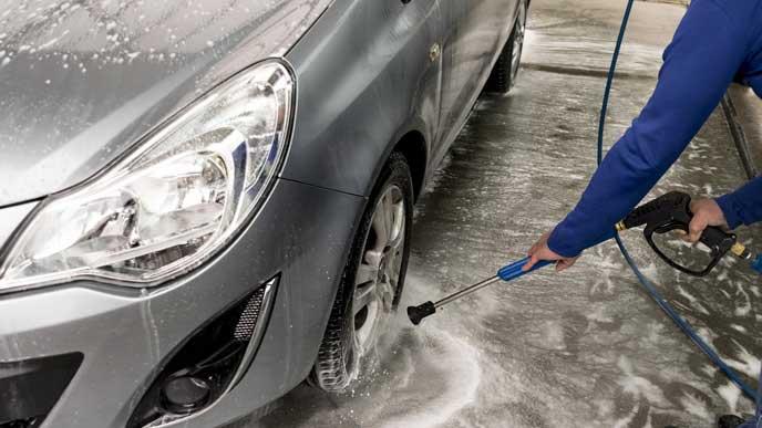 洗車で融雪剤を洗い落とすドライバー