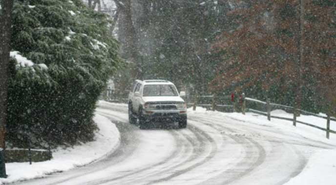 雪の積もる山道を登る車