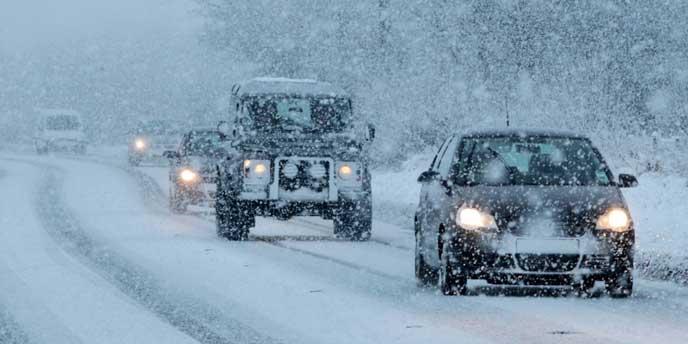 夜間に雪道を走る車