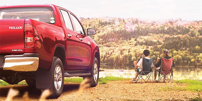 駐車中のハイラックスと椅子に座っている2人の男