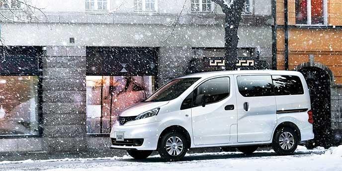 雪の降る街を走るNV200バネットバン