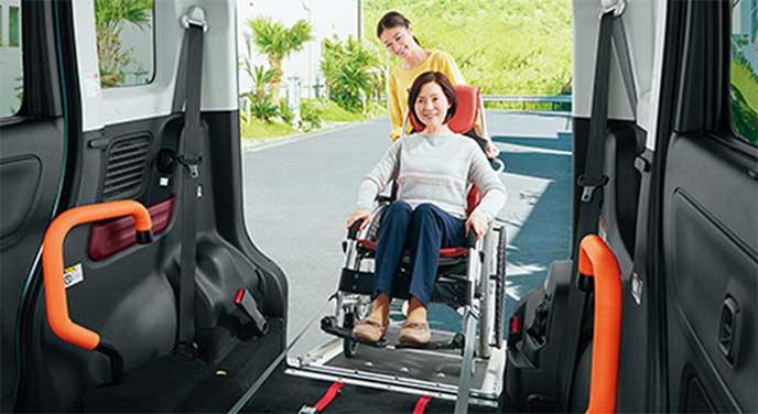 スペーシアのスロープを使って乗車する車いすに座っている女性と介助者