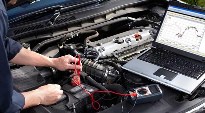 車のバッテリーを点検する整備士