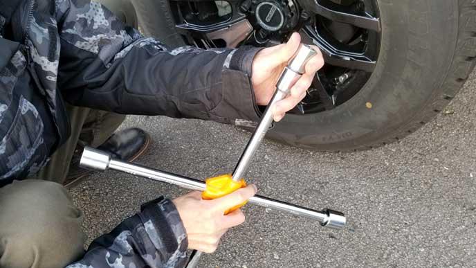 専用工具を十字レンチにはめる男性