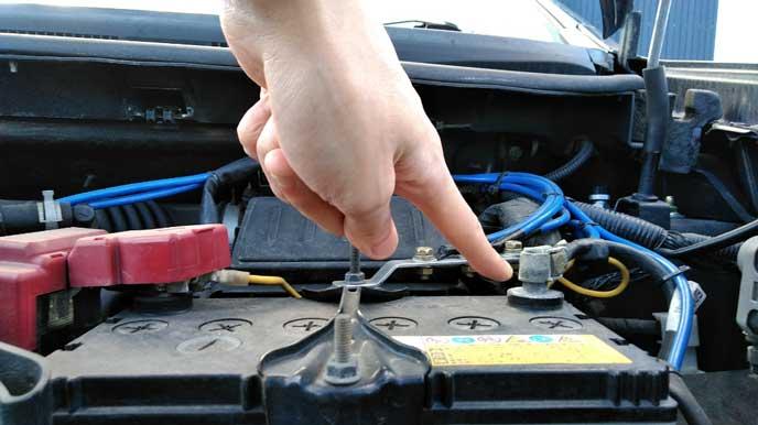 バッテリーのマイナス端子を指さす男性