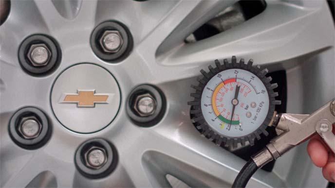 電動エアコンプレッサーについているエアゲージでタイヤの空気圧を測っているところ
