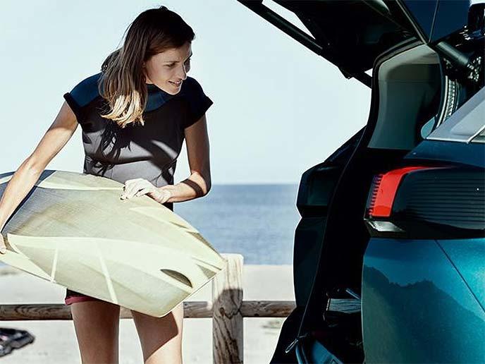 ハンズフリー電動テールゲートを使ってサーフボードを出し入れする女性