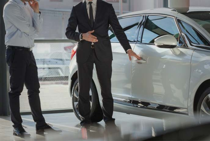 展示車両を前に思案する男性とセールス