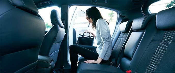ホンダ・ヴェゼルのリアシートに着座しようとしている女性