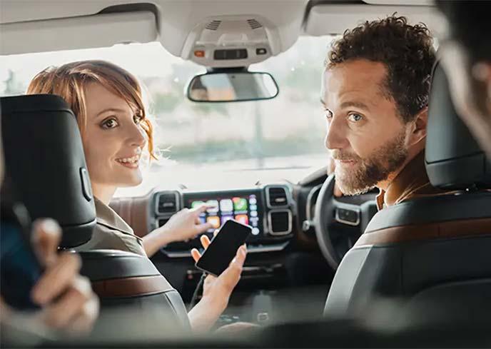 スマホを操作しながら後席の人に話しかける助手席の女性と振り返るドライバーの男性