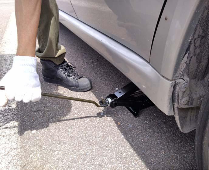 ジャッキの丸い部分にハンドルをつけてぐるぐると回して車体を持ち上げていく