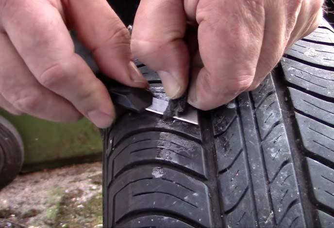 タイヤのパンク穴に埋めた余分な補修ラバーを切り取っているところ