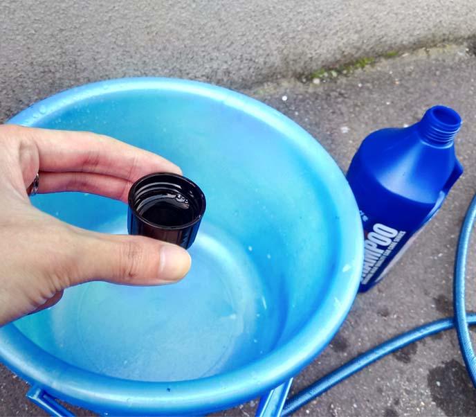 洗剤を入れたキャップと水の入ったバケツ