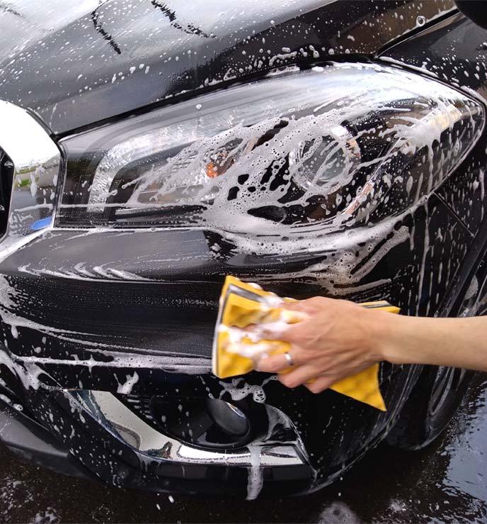 泡立てたスポンジでフロントバンパーを洗っているところ