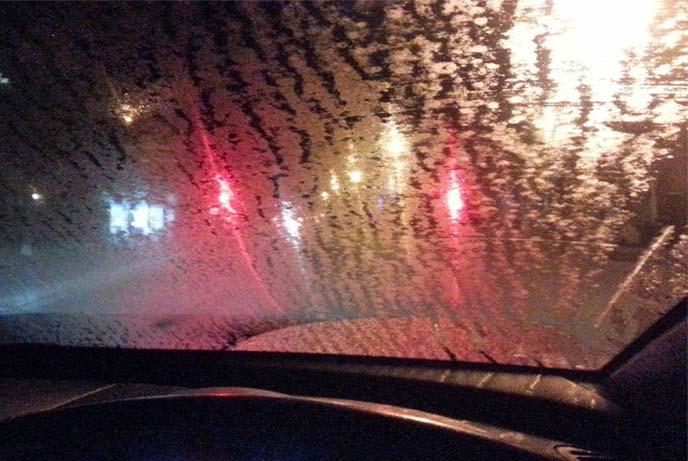対向車のヘッドライトが油膜で乱反射して視界不良となったフロントガラス