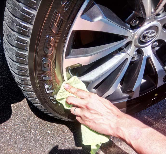 ホイールに付着したタイヤワックスをウエスで拭き取っている様子