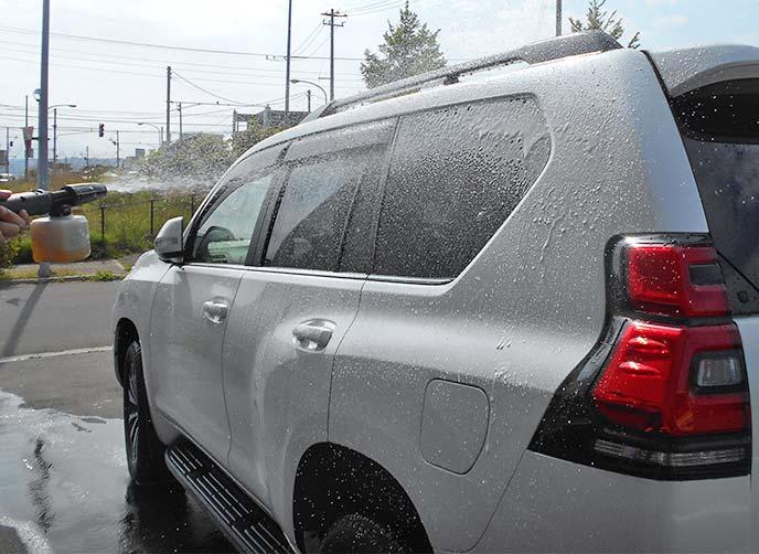 高圧洗浄機で車を泡洗浄している様子