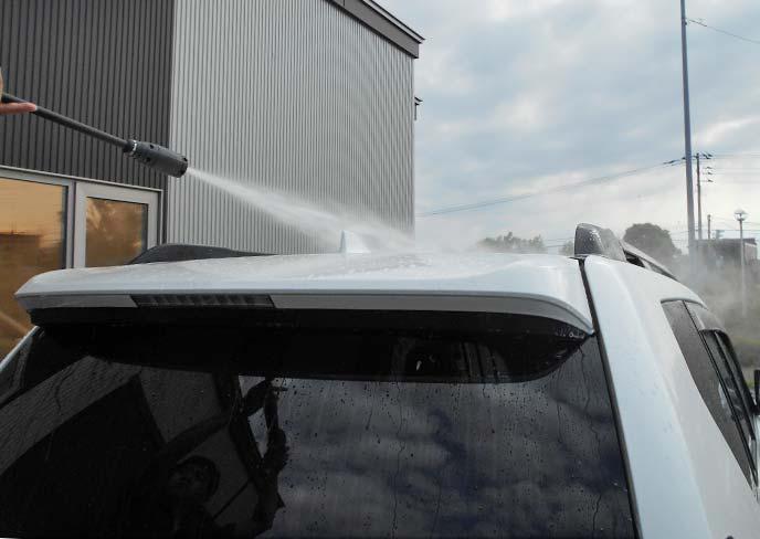 高圧洗浄機でルーフを水洗いしている車