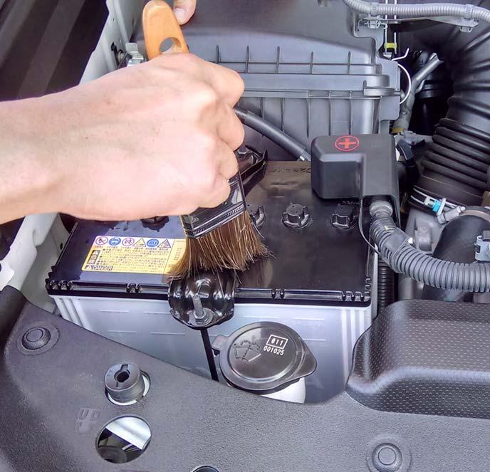 バッテリー金具をハケで掃除しているところ