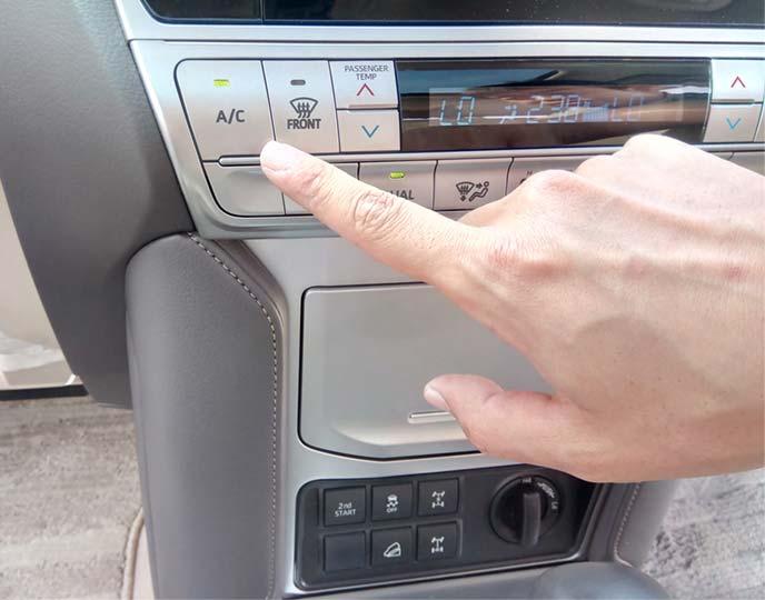 エアコンの作動ボタンを押そうとしている指