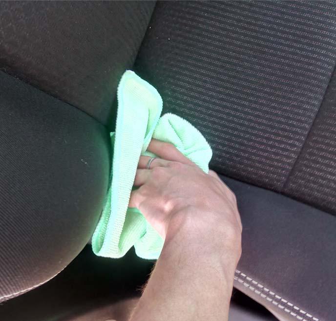 ウエスでフロントシート背もたれの下部を拭いているところ