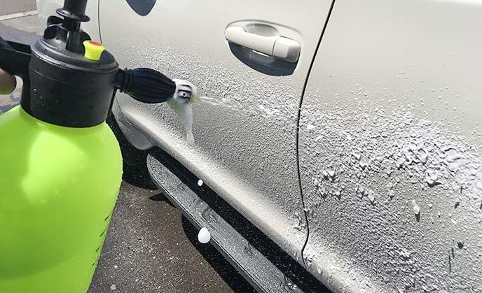 洗車フォームガンで車のドアに泡を吹きつけている様子