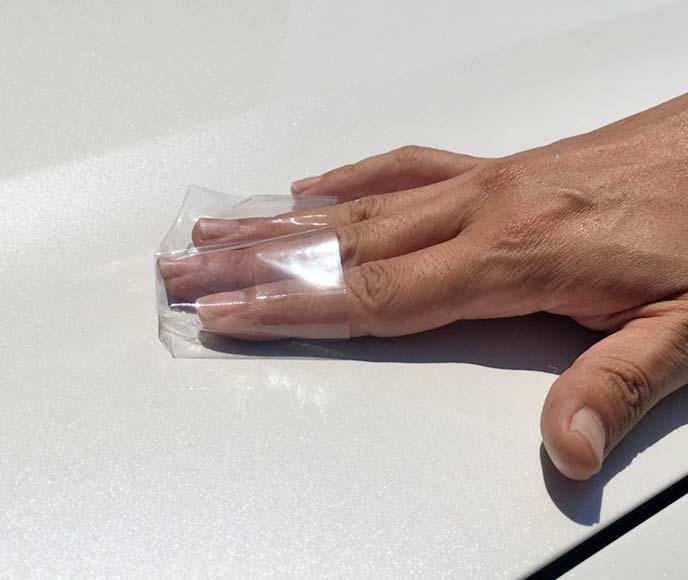 指先にはめた透明フィルムで車のボンネットを撫で鉄粉を確認している様子