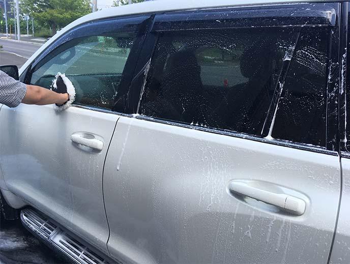 洗車スポンジで左窓の泡を一定方向に拭き伸ばしているところ