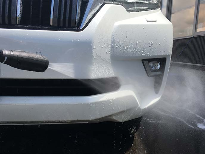 ランドクルーザープラドのフロントフェンダーを噴霧洗浄しているところ