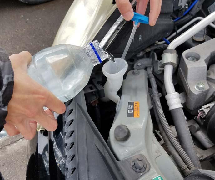 ポリ容器にいれた水道水を補充口に注いでい様子