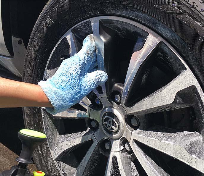 洗剤を付けた速乾ヘアドライ手袋でアルミホイールのスポークを洗っているところ