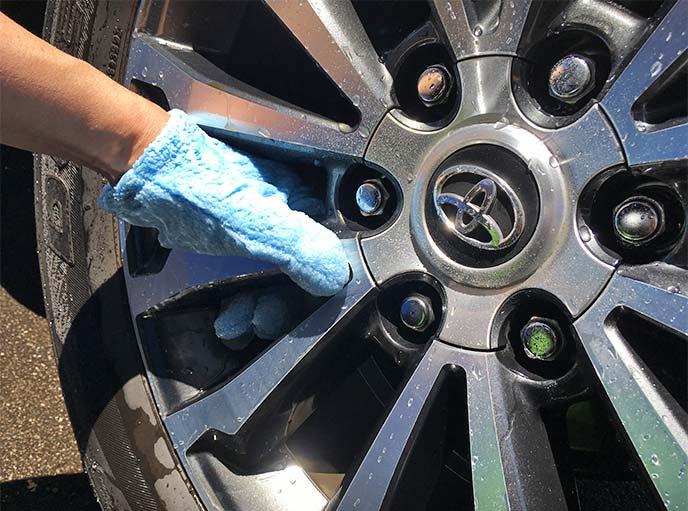 速乾ヘアドライ手袋でアルミホイールスポークの裏側を洗っている様子