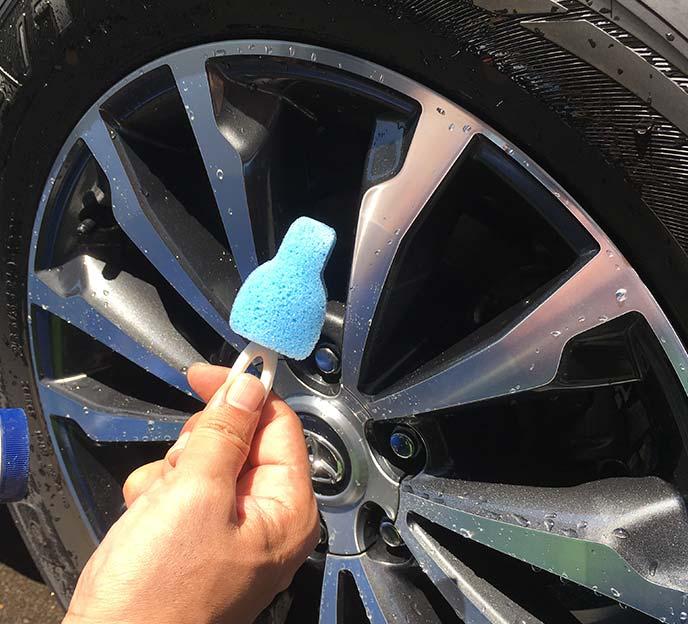 タイヤの前で手にした「哺乳瓶洗いスポンジ」のミニスポンジ