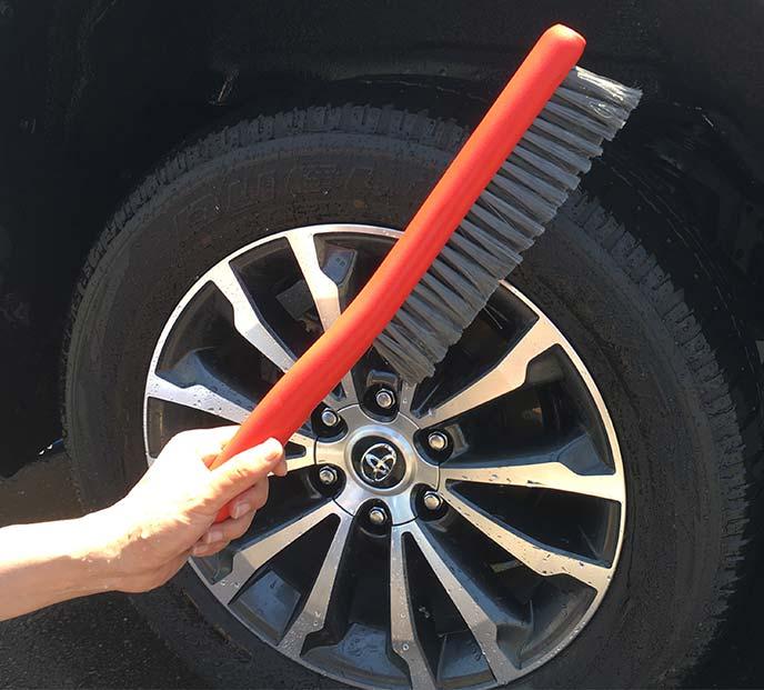 タイヤの前で「洗車ブラシ やわらかを手にしているところ