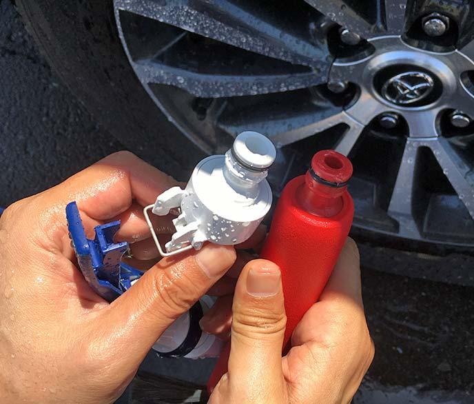 ホースのジョイントと「洗車ブラシ やわらか」の注水口を並べて手にしている様子