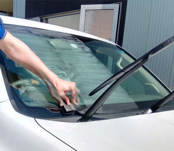 フロントガラスにウロコ取りクリーナーを塗布している様子