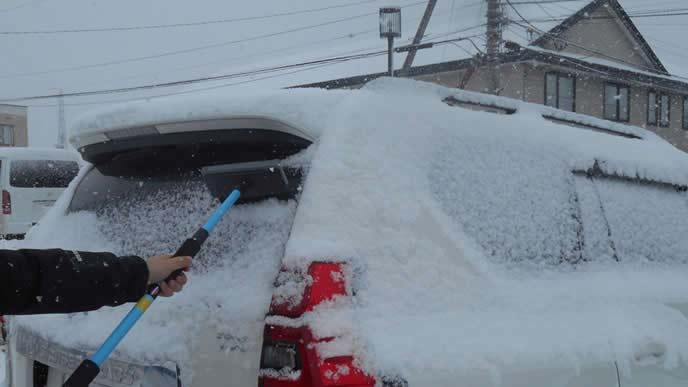 リヤガラスの雪を下ろす男性