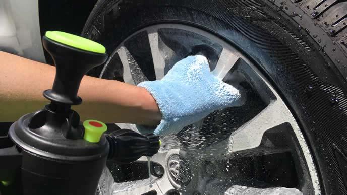 車のホイールを磨く男性